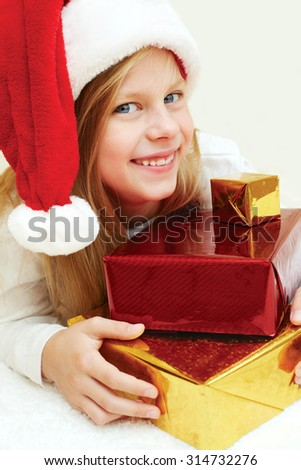 Beautiful blonde little girl holds Christmas presents. Look at the camera.