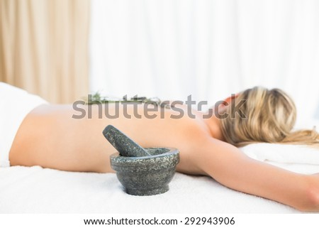 Beautiful blonde lying on massage table with mortar and pestle at the health spa - stock photo
