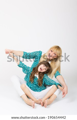 Beautiful blonde mother and cute five year old daughter sitting holding hands playing together wearing matching clothes.  - stock photo