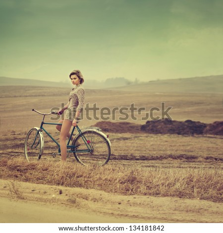 beautiful blonde on a bicycle. vintage photo - stock photo
