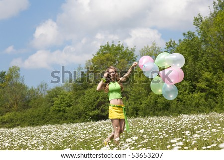 beautiful blonde on chamomile field with balloons - stock photo
