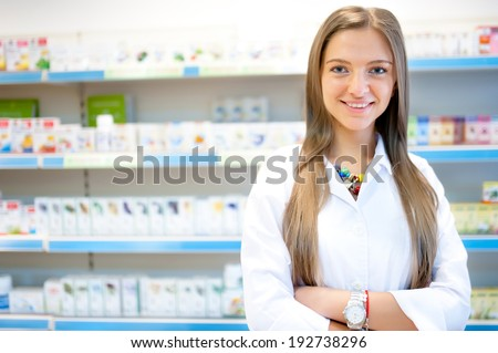 Beautiful blonde pharmacist in drugstore or pharmacy smiling. Portrait of health care doctor in pharmacy - stock photo
