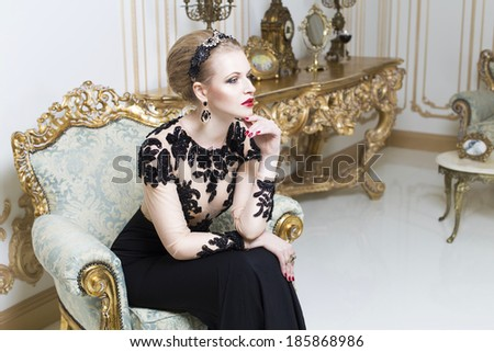 Beautiful blonde royal woman sitting on a retro chair in gorgeous luxury dress. Indoor. Copy Space - stock photo