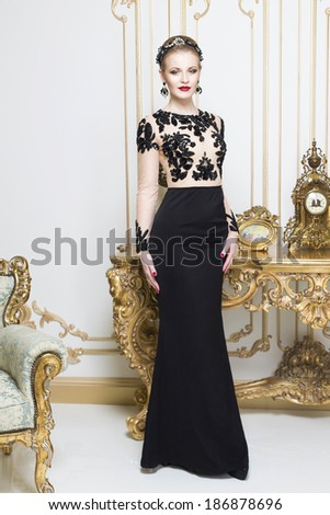 Beautiful blonde royal woman standing near retro table in gorgeous luxury dress. Indoor - stock photo