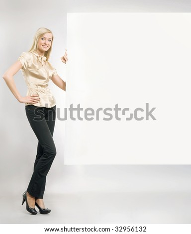 beautiful blonde secretary showing an empty board,lots of copyspace - stock photo