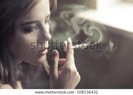 beautiful blonde smokes at home - stock photo