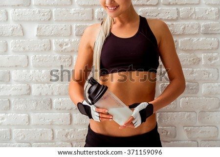 Beautiful blonde sportswoman in sports gloves smiling, looking down and holding a shaker with sports nutrition, standing against white brick wall, close-up - stock photo