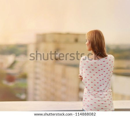 Beautiful blonde stands on the edge of the roof - stock photo