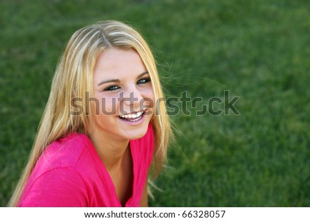beautiful blonde teen girl smiling in grass - stock photo
