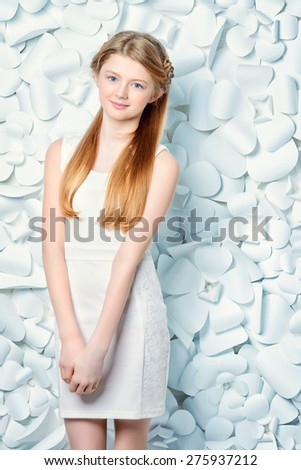 Beautiful blonde teen girl wearing white dress posing by a background of white paper flowers. Beauty, fashion.  - stock photo