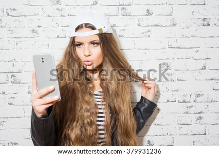 Beautiful blonde teenage girl in white cap, leather jacket taking a selfie on smartphone, posing, making a kissy face, standing against white brick wall. Copy space, retouched, no filter. - stock photo