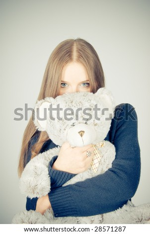 Beautiful blonde teenager holding a teddy bear