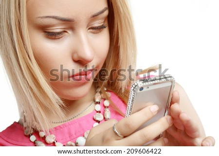 Beautiful blonde using mobile telephone or smartphone and smiles in doubt