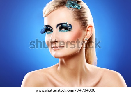 Beautiful blonde with artistic makeup over blue background