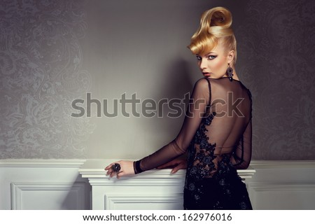 beautiful blonde with creative hairstyle wearing gorgeous evening dress - stock photo