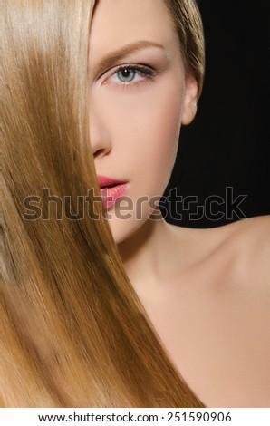 Beautiful blonde with straight hair on dark background - stock photo