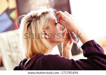 beautiful blonde woman applying false lashes to herself - stock photo