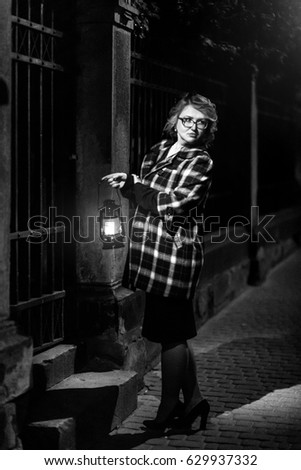 Beautiful blonde woman detective in stylish retro coat holding old lantern, french noire atmosphere concept