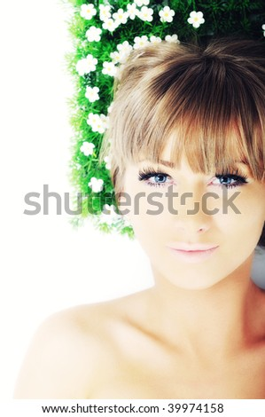 beautiful blonde woman face isolated on white with small green peace of grass