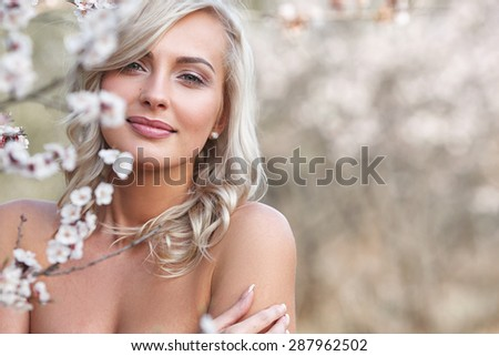 beautiful blonde woman head and shoulders portrait in a flowered spring garden - stock photo