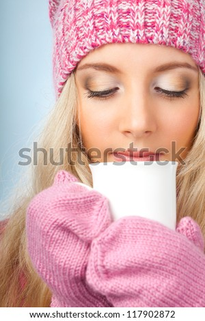 beautiful blonde woman holding white cup of drink over blue - stock photo