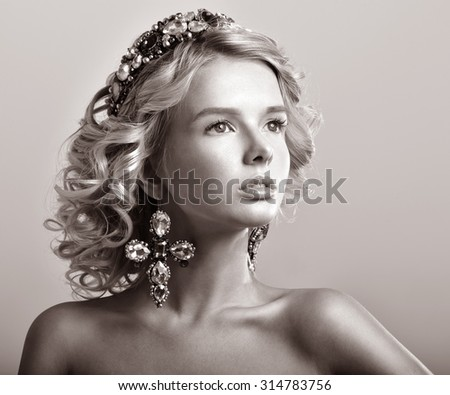 Beautiful blonde woman in a luxurious tiara and earrings. Diadem with Jewels.