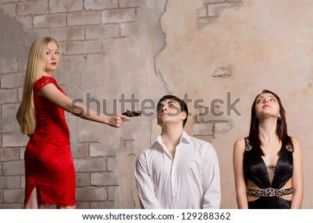 Beautiful blonde woman in a red dress threatening two young hostages who are kneeling in front of her with a handgun - stock photo