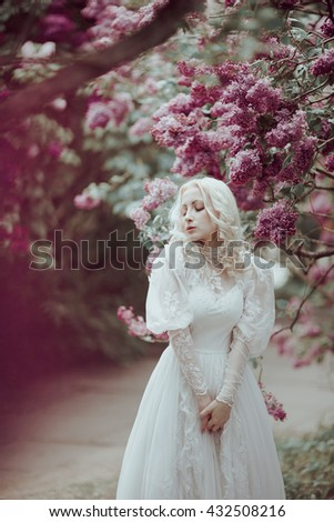 Beautiful blonde woman in blooming lilac garden. Vintage bride concept - stock photo