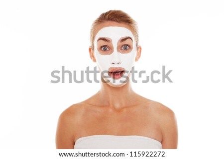 Beautiful blonde woman in face mask and towel with a surprised wide eyed expression isolated on white