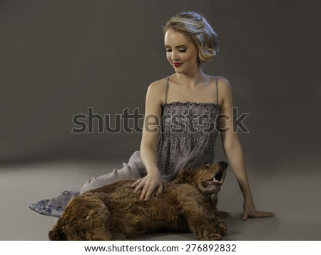 Beautiful blonde woman in grey dress seated next to adorable Spaniel dog - stock photo