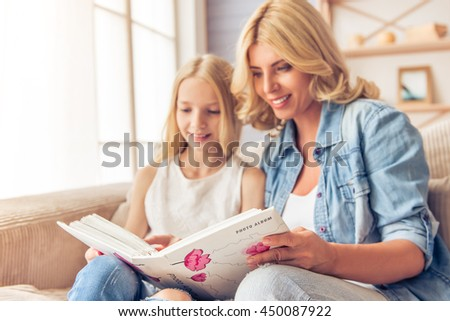 Beautiful blonde woman in jeans shirt and her teenage daughter are looking through photos and smiling while sitting on couch at home. Photo album in focus - stock photo
