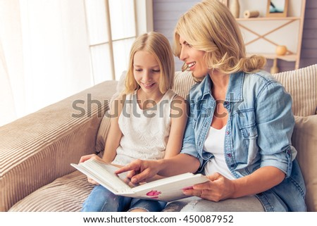 Beautiful blonde woman in jeans shirt and her teenage daughter are looking through photos and smiling while sitting on couch at home - stock photo