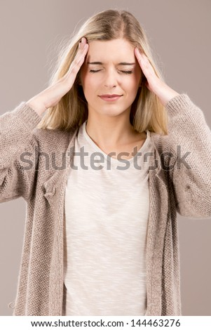 Beautiful blonde woman in pain with a big headache - stock photo