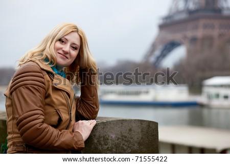 Beautiful blonde woman in Paris, on the Seine embankment - stock photo