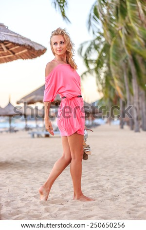 Beautiful Blonde Woman In Pink Dress Posing on the Beach - stock photo