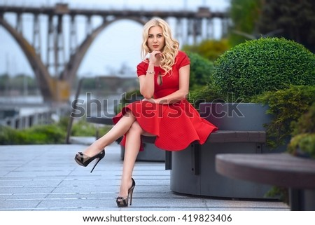 Beautiful blonde woman in red dress and high heels is sitting outdoor on the bench at the evening.  - stock photo