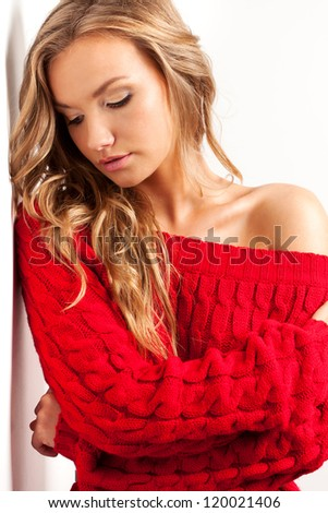beautiful blonde woman in red dress looking down near wall - stock photo