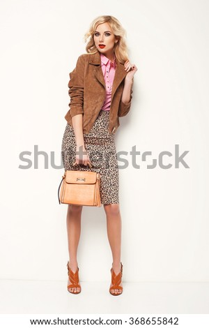 Beautiful blonde woman in stylish clothes posing in the studio, long hair, holding handbag, high heels shoes. Fashion photo