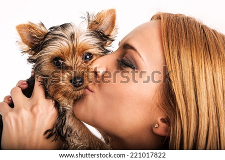 Beautiful blonde woman kissing yorkshire terrier - close up - stock photo