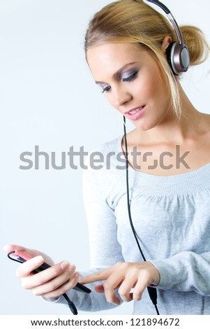 Beautiful blonde woman listening to music at home