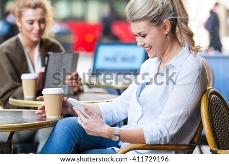 Beautiful blonde woman looking at smart phone and drinking a coffee at a cafe in London. There is another woman with a digital tablet on background. Business and lifestyle concepts - stock photo