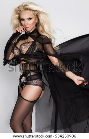 Beautiful blonde woman model with disheveled long hair and dispelled black silk dress