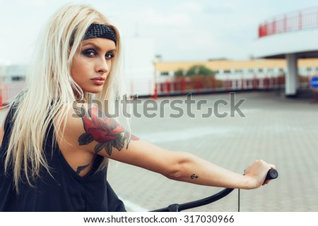 beautiful blonde woman on bike in city. Soft sunny color outdoors portrait - stock photo