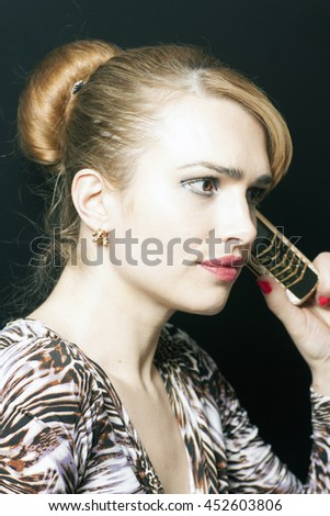 Beautiful blonde woman or businesswoman talking on a cell phone on black background