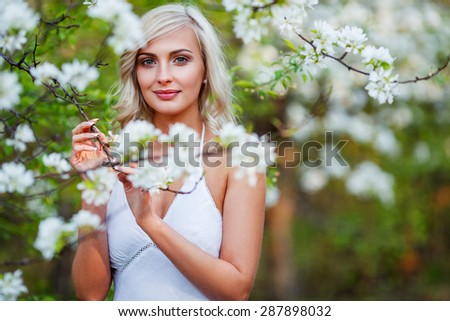 beautiful blonde woman portrait in a flowered spring garden during sunset - stock photo