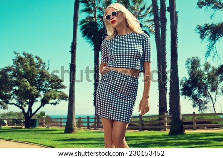 beautiful blonde woman posing in fashion clothes and jewelry among palm trees. Fashion photo with sunglasses - stock photo