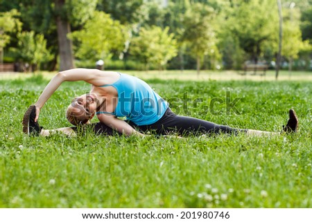 Beautiful blonde woman practicing yoga in the park,Yoga-Parivrtta Janu Sirsasana/Revolved Head-to-Knee Pose - stock photo