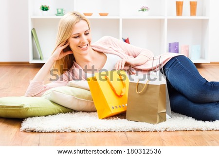 Beautiful blonde woman resting at her home after shopping,Shopping - stock photo