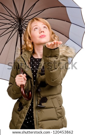 Beautiful blonde woman sheltering under a large umbrella holding out her hand testing for rain as she looks up at the sky isolated on white - stock photo
