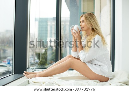 beautiful blonde woman sitting comfortably on a balcony, wearing men's shirt holding a coffee - stock photo